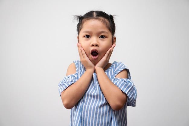 Portret azjatyckiego dziecka i do zebrania włosów i połóż tutaj ręce na policzkach i podekscytowanej pozie