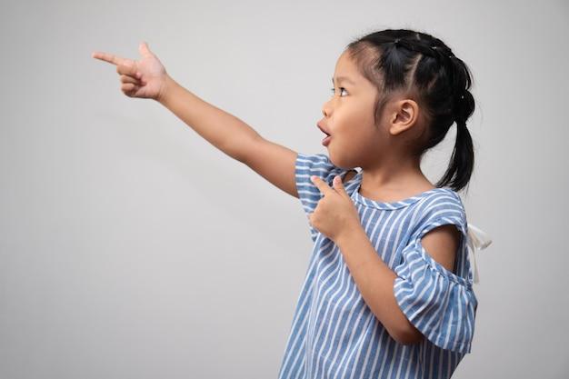 Portret azjatyckiego dziecka i zebrać włosy i unieść palec wskazujący w powietrze i wykonać myślącą podekscytowaną pozę