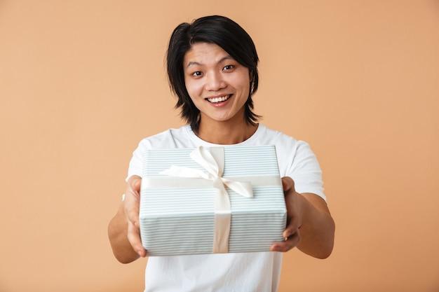 Portret azjatyckiego faceta noszącego białą koszulkę uśmiechającego się i trzymającego pudełko na białym tle nad beżową ścianą