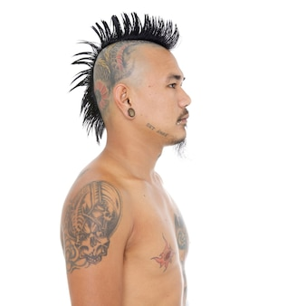 Portret azjatyckiego faceta punkowego z fryzurą irokezem, tatuażem na głowie, przekłuciem warg i uszu na białym tle na białym tle