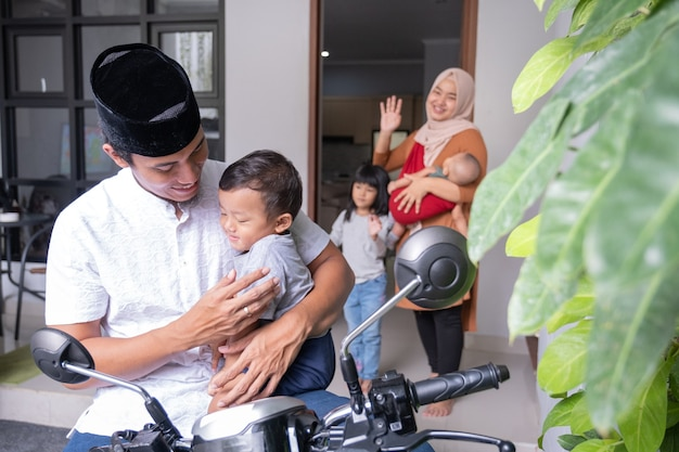 Portret azjatyckiego męża żegnającego się z rodzinnym dzieckiem i żoną przed wyjazdem motocyklem