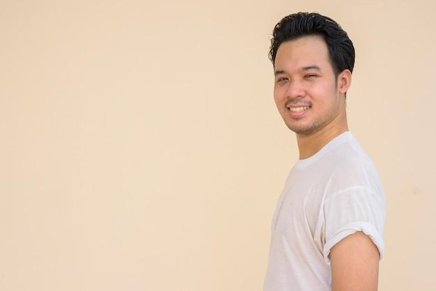 Portret azjatyckiego mężczyzny noszącego białą koszulkę na prostym tle na zewnątrz, podczas gdy się uśmiecha