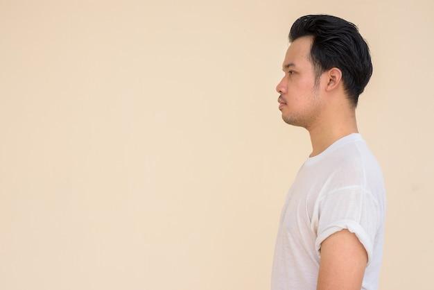 Portret azjatyckiego mężczyzny noszącego dorywczo białą koszulkę na prostym tle na zewnątrz