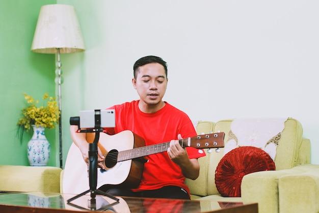 Portret azjatyckiego mężczyzny, śpiewającego i grającego na gitarze podczas nagrywania przez inteligentny telefon w domu