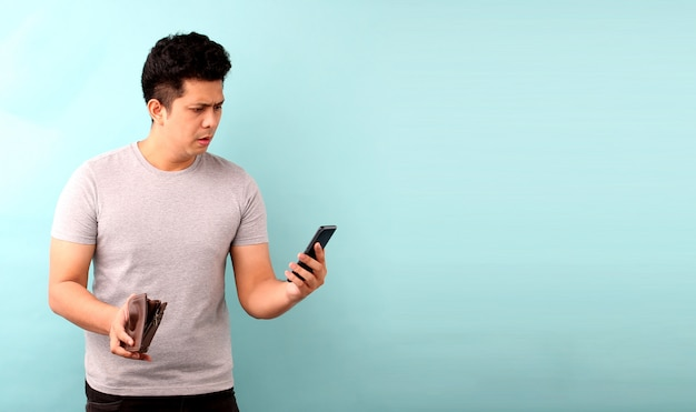 Portret azjatyckiego mężczyzny trzymającego telefon komórkowy zszokowany, zaskoczony zaniemówiony. trzymając pusty portfel na niebieskiej ścianie.