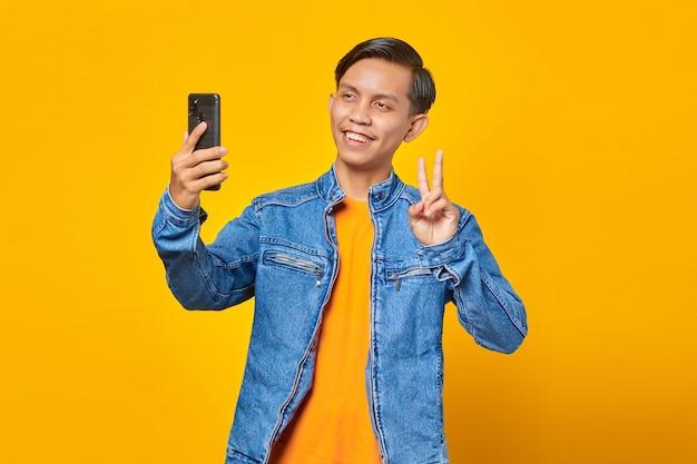 Portret azjatyckiego mężczyzny uśmiechającego się i pokazującego znak pokoju podczas robienia selfie na telefonie komórkowym na białym tle na żółtym tle