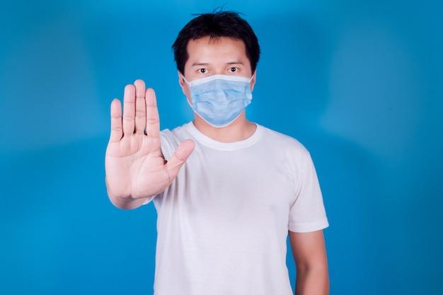 Portret azjatyckiego mężczyzny w medycznej masce na twarz w celu ochrony covid-19 pokaż gest zatrzymania rąk do zatrzymania epidemii wirusa koronowego, na niebieskim tle
