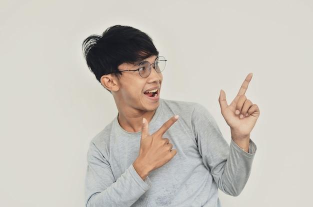 Portret azjatyckiego mężczyzny w okularach wskazujących na pustą przestrzeń
