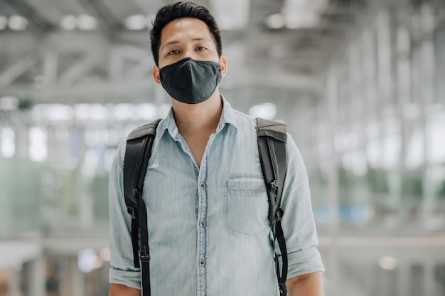 Portret azjatyckiego mężczyzny z maską chroniącą przed koronawirusem w niebieskiej koszuli stojącej z plecakiem i patrzącej na kamerę