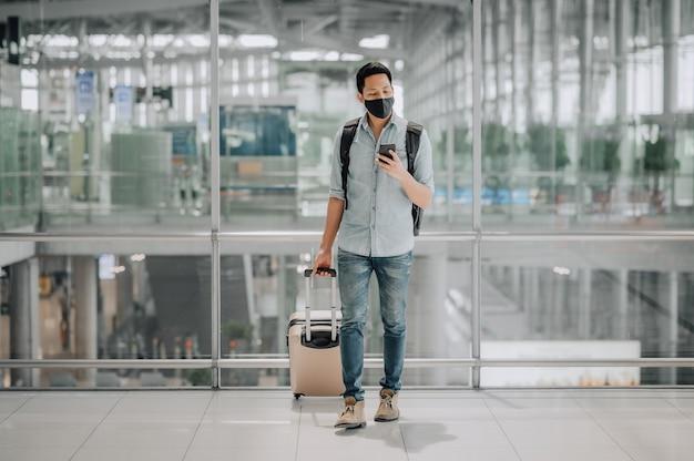 Portret azjatyckiego mężczyzny z maską chroniącą przed koronawirusem w niebieskiej koszuli z bagażem przy użyciu smartfona podczas chodzenia