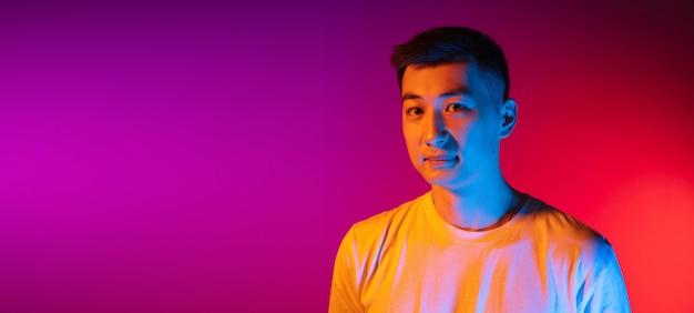 Portret azjatyckiego młodego mężczyzny na białym tle na ścianie w gradientowym zielonym żółtym świetle neonowym.