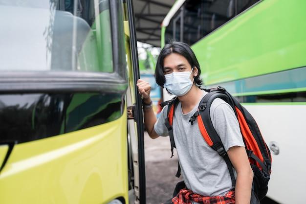 Portret azjatyckiego młodzieńca z maską, jazda autobusem