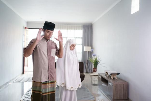 Portret azjatyckiego muzułmanina modlącego się przez fałdowe ramię przed klatką piersiową w domu