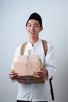 Portret azjatyckiego muzułmańskiego mężczyzny przeciwko na szaro na sobie muzułmańskie ubrania i trzymając pudełko z plecakiem