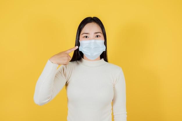 Portret azjatyckiego nastolatka noszącego i wskazującego medyczną maskę na twarz w celu ochrony covid-19 (koronawirusa) na żółtym tle