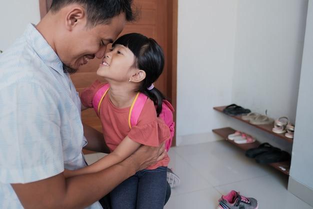 Portret azjatyckiego ojca obejmuje swoją córkę przed pójściem do szkoły rano