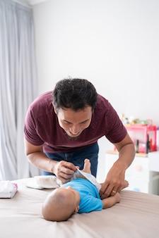 Portret azjatyckiego ojca zmieniającego pieluchę dla niemowląt w domu