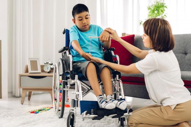Portret azjatyckiego opiekuna fizjoterapeuty pomaga i bawi się ze specjalnym problemem zdrowotnym niepełnosprawnego dziecka, wykonując ćwiczenia siedząc na wózku inwalidzkim w klinice rehabilitacyjnej. pojęcie opieki niepełnosprawności
