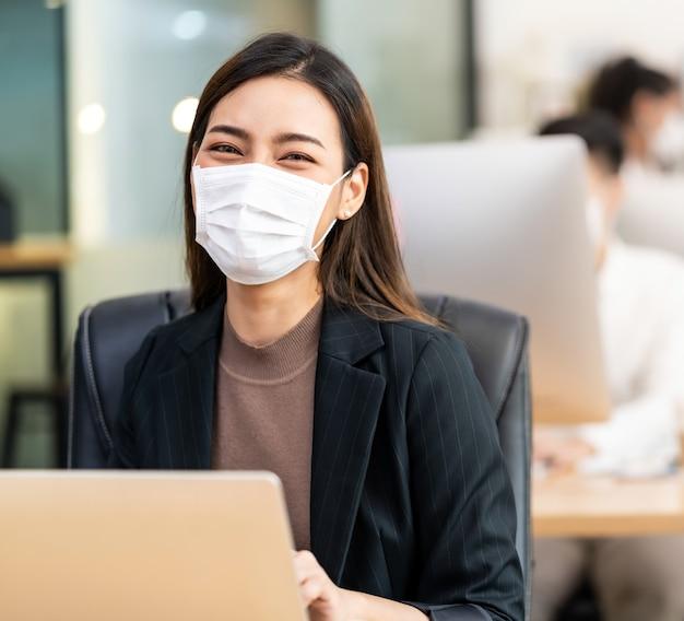 Portret azjatyckiego pracownika biurowego, który nosi ochronną maskę na twarz, pracuje w nowym normalnym biurze z międzyrasowym kolegą w tle, ponieważ praktyka dystansu społecznego zapobiega koronawirusowi covid-19.