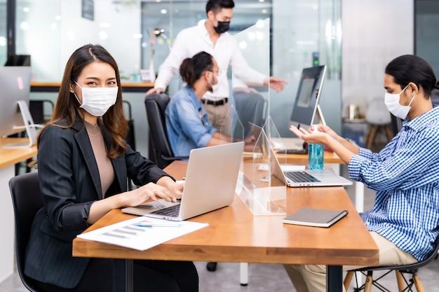 Portret azjatyckiego pracownika biurowego, który nosi ochronną maskę na twarz, pracuje w nowym normalnym biurze z zespołem międzyrasowym w tle, ponieważ praktyka dystansu społecznego zapobiega koronawirusowi covid-19.