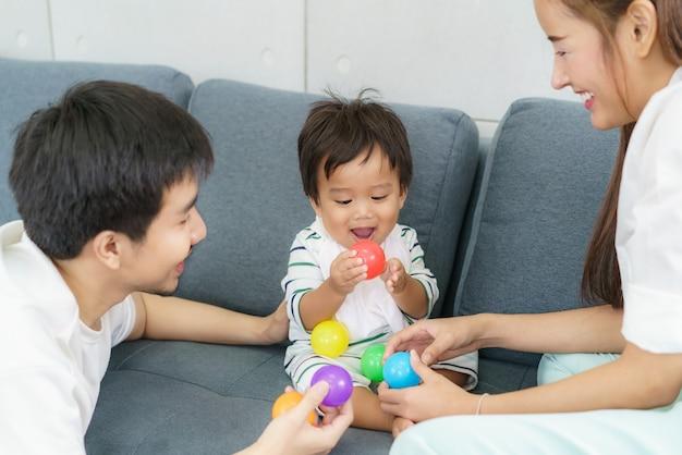Portret azjatyckiego słodkiego chłopca bawiącego się w kolorowe plastikowe kulki z ojcem i matką na kanapie z radosną buźką i uśmiechając się do nauki kolorów w domu.