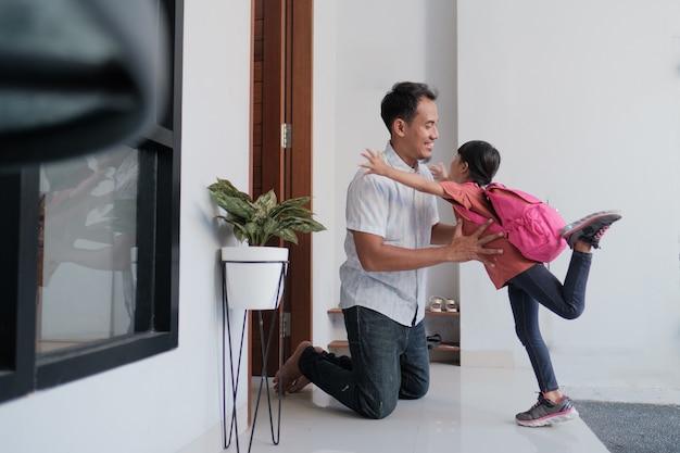 Portret azjatyckiego szczęśliwego ojca witającego swoje dziecko po ukończeniu szkoły