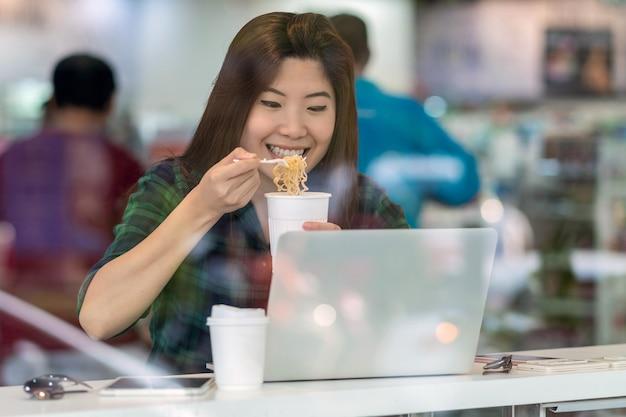 Portret azjatyckiej bizneswoman w swobodnym garniturze jedzącej makaron z akcją szczęścia