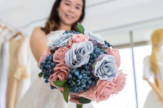 Portret azjatyckiej damy uśmiechnięty mienie kwiat w panny młodej sukni.