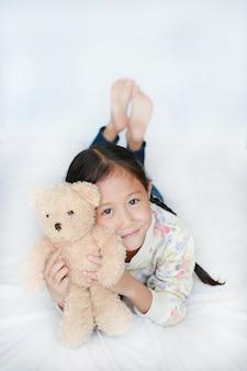 Portret azjatyckiej dziewczynki przytulanie brązowego misia na łóżku