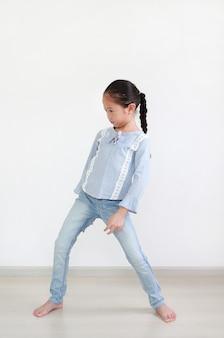 Portret azjatyckiej dziewczynki stojącej postawy w pokoju przed białą ścianą