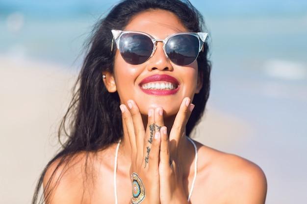 Portret azjatyckiej dziewczyny tajskiej zabawy na tropikalnej plaży z okularami przeciwsłonecznymi