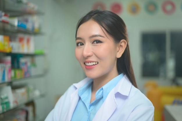 Portret azjatyckiej farmaceuty kobieta ubrana w fartuch laboratoryjny w nowoczesnej aptece aptece