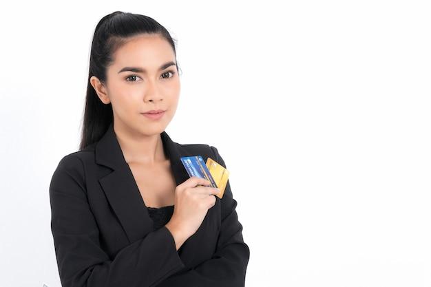 Portret azjatyckiej kobiety biznesu pokazujący kilka banknotów pieniędzy i trzymający w ręku kartę kredytową na białym tle na białej powierzchni