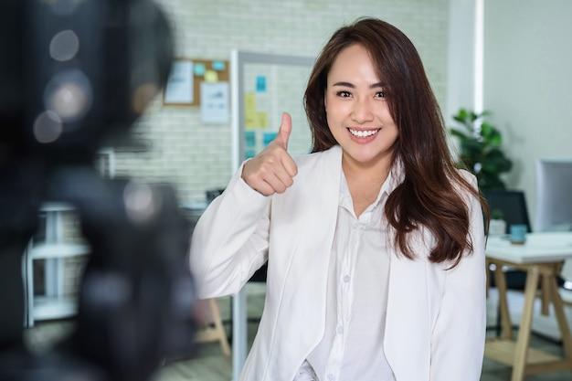 Portret azjatyckiej kobiety biznesu z kciukami do góry, jak podczas nagrywania wideo w celu uzyskania wpływu społecznego