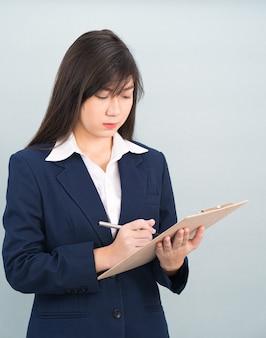 Portret azjatyckiej kobiety długie włosy i ubrany w garnitur ze schowka i pióra w rękach myśli o sukcesie, na białym tle