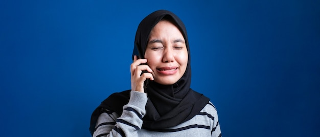 Portret azjatyckiej kobiety muzułmańskiej dostać złe wieści na telefon, smutny płacz wypowiedzi. na niebieskim tle