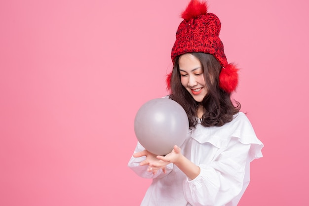 Portret azjatyckiej kobiety na białej koszuli i czerwonym kapeluszu, trzymając w ręku balon. szczęśliwy model uśmiechnięty na różowo