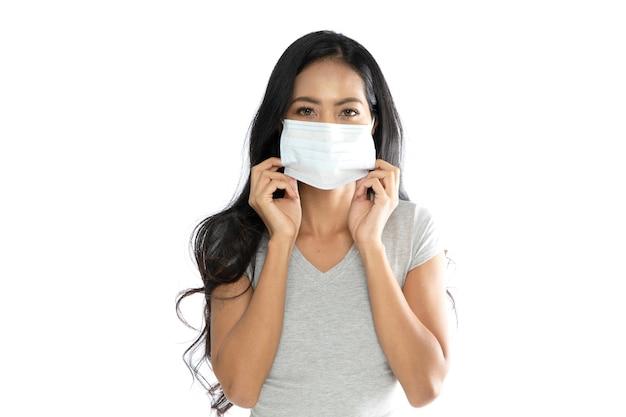 Portret azjatyckiej kobiety noszącej medyczną maskę przeciw grypie, aby zapobiec koronawirusowi