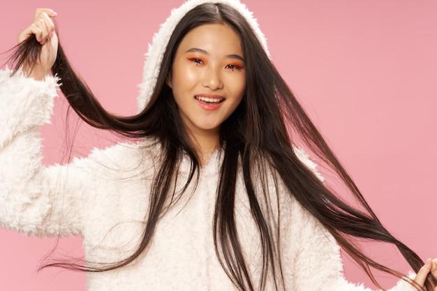 Portret azjatyckiej kobiety o ciemnych włosach w białym swetrze z kapturem na różowym tle