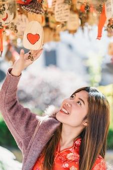 Portret azjatyckiej kobiety podróżnik patrzący na amulet z dzwonkiem z chińskim językiem na starym mieście w lijiang
