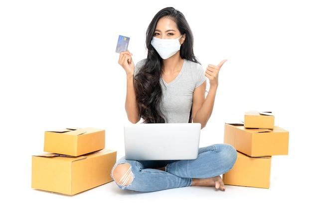 Portret azjatyckiej kobiety siedzi na podłodze z wieloma pudełkami z boku