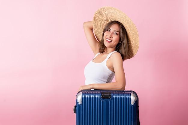 Portret azjatyckiej kobiety w kapeluszu z szerokim rondem i letnich ubraniach stojącej z walizką