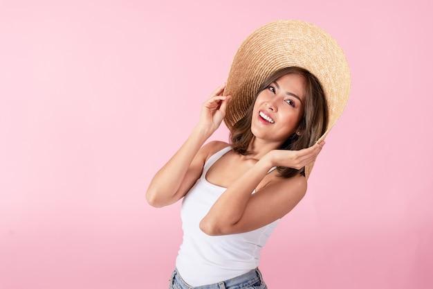 Portret azjatyckiej kobiety w kapeluszu z szerokim rondem i letnich ubraniach