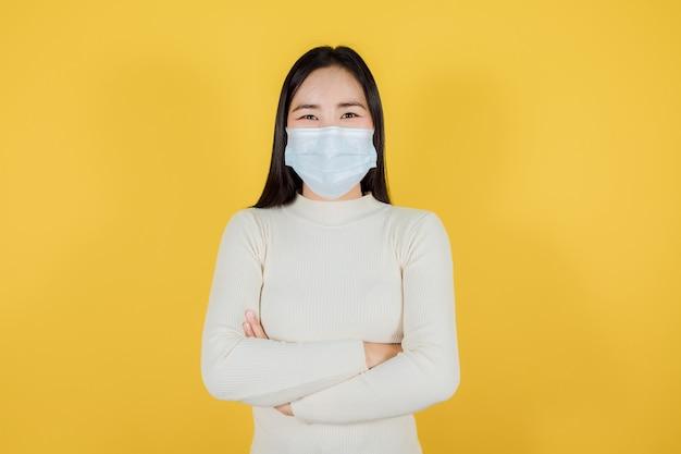 Portret azjatyckiej kobiety w medycznej masce na twarz w celu ochrony covid-19 (koronawirus) nosi kremowy sweter stojący skrzyżowanymi rękami na żółtym tle