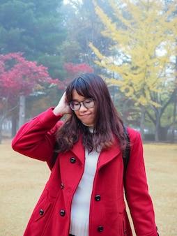 Portret azjatyckiej kobiety w okularach w czerwonym jesiennym płaszczu czuje się przygnębiony, smutny i znudzony