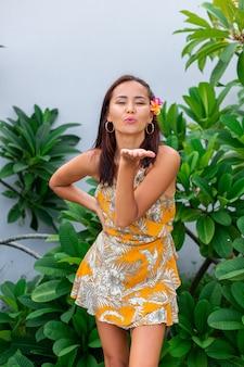 Portret azjatyckiej kobiety w żółtej letniej sukience stoi z kwiatem plumeria thai we włosach i okrągłych kolczykach