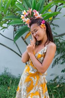 Portret azjatyckiej kobiety w żółtej letniej sukience stoi z plumeria thai kwiat we włosach