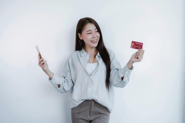 Portret azjatyckiej kobiety z długimi włosami, trzymającej czerwoną kartę kredytową i smartfona