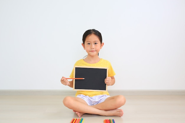 Portret azjatyckiej małej dziewczynki siedzącej w pomieszczeniu trzymającym tablicę i wskazującym kolorowy ołówek na pustej przestrzeni na pokładzie
