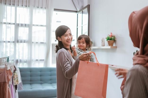 Portret azjatyckiej matki kupującej ubrania podczas zakupów z jej maluchem